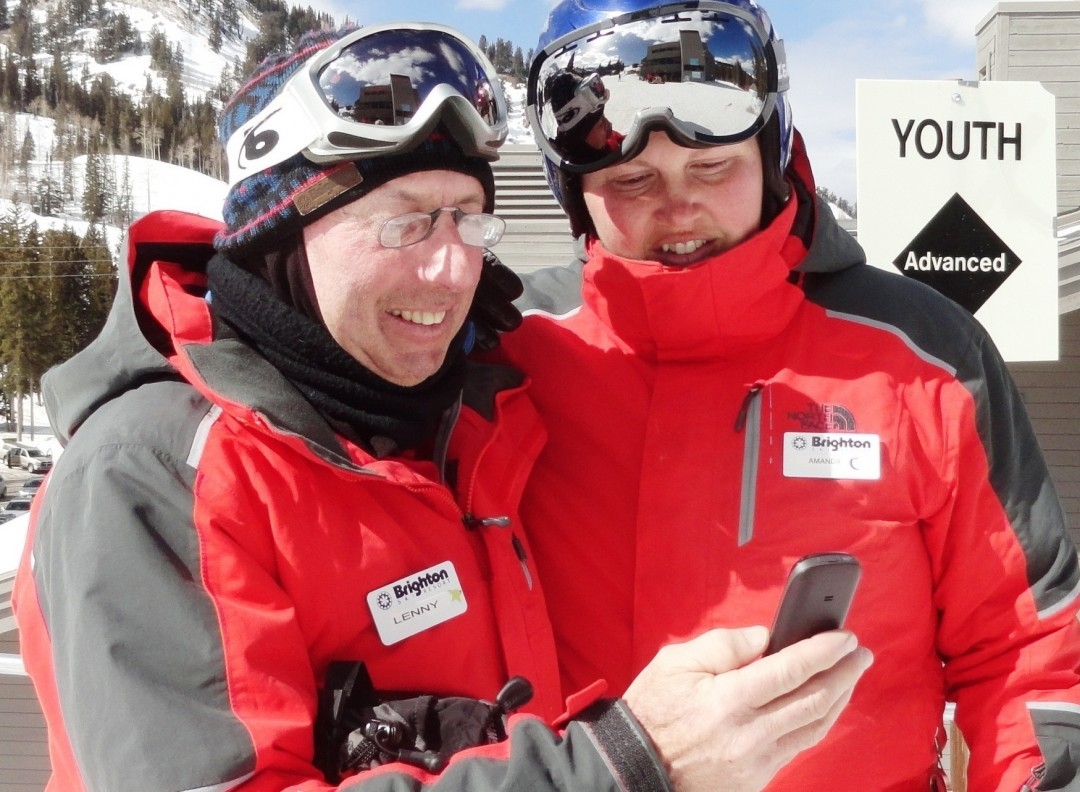 Brighton Resort ski instructors Lenny Bernstein and Amanda Cimini check the phone. Lenny is wearing ThinOptics. Credit: Harriet Wallis