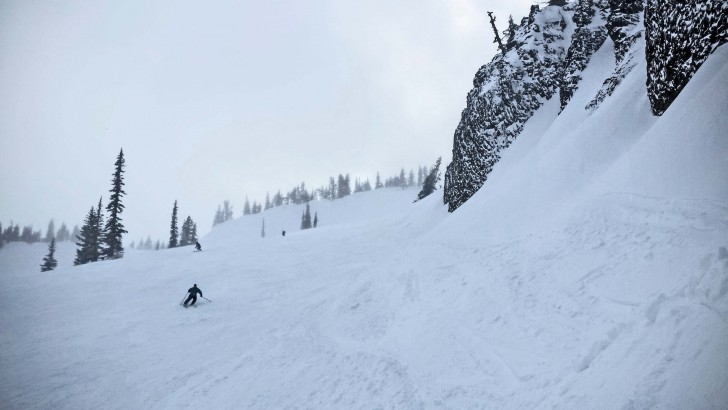 Skiers drop under the cliffs on Bomber Bowl, one of Mission Ridge's signature runs. Credit: John Nelson