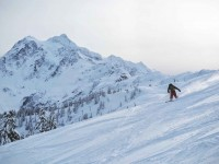 With Mount Shuksan looming behind, a snowboarder shreds soft snow at Mt. Baker Ski Area. Credit: John Nelson