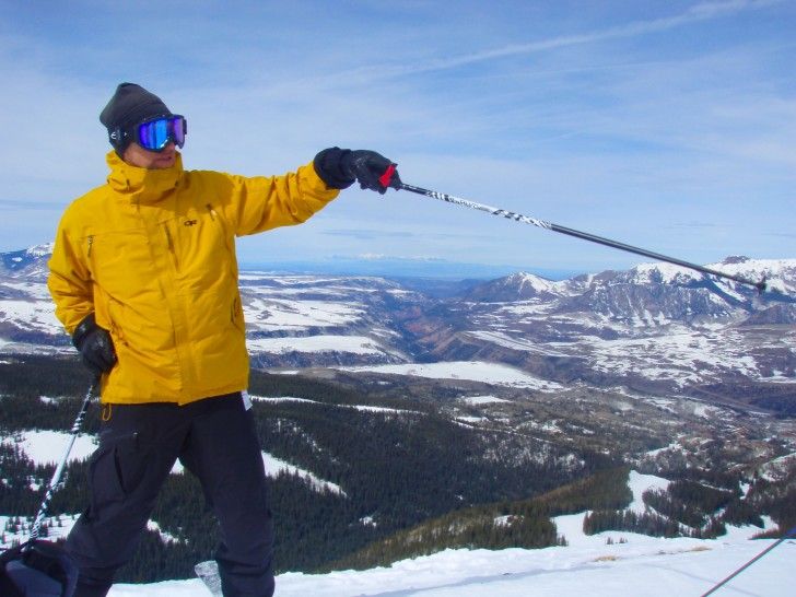 Guide Peter McCarville pointing out a geologic feature, his ski pole framing a view of the distant LaSalle Mts. of Utah. Credit: Jan Harold Brunvand