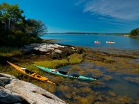 Dick Gilbane (rowing) and Kristen Roos (paddling) pass Little Ram Island in the Sheepscot River. Credit: Tamsin Venn