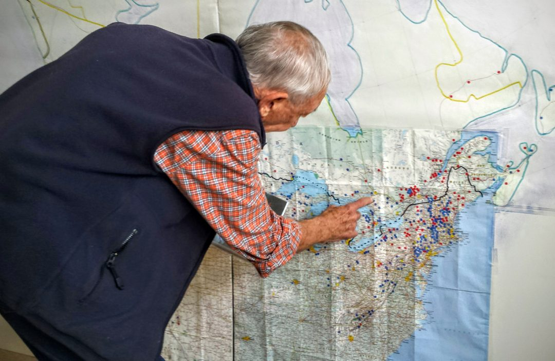 John Andrew points out ski areas he's skiied on a the wall-sized map in his Renton, Wash., home. Credit: John Nelson