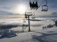 Skiers and snowboarders rise above the clouds on the Crystal Chair at Sun Peaks. Credit: John Nelson