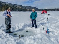 Ice fishing on Heffley Lake near Sun Peaks Resort with Elevated Fishing Adventures. Here, the guide and guest try their hand at outdoors holes. Credit: Yvette Cardozo
