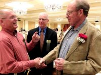Honoree Howard Peterson (r) is warmly congratulated by Ski Archives Advisory Board members Tom Nielson (l) and Richard Hughes. Credit: Harriet Wallis